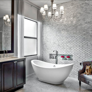 Design ideas for a large classic ensuite bathroom in Miami with raised-panel cabinets, dark wood cabinets, a freestanding bath, grey tiles, stone tiles, grey walls, marble flooring, marble worktops and a submerged sink.