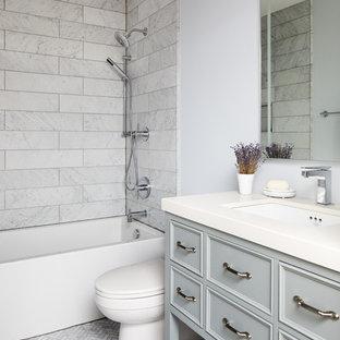 Modelo de cuarto de baño infantil, clásico renovado, de tamaño medio, con armarios con paneles empotrados, puertas de armario azules, bañera empotrada, ducha empotrada, baldosas y/o azulejos grises, baldosas y/o azulejos de mármol, suelo de mármol, encimera de cuarzo compacto, suelo gris, paredes azules y lavabo bajoencimera