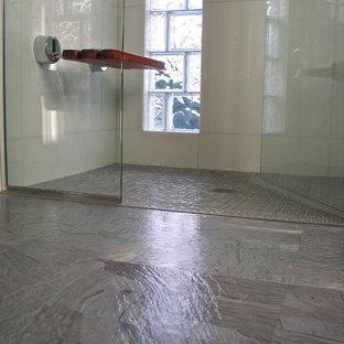 Exempel på ett litet modernt en-suite badrum, med ett undermonterad handfat, släta luckor, skåp i mellenmörkt trä, bänkskiva i kvarts, en kantlös dusch, en toalettstol med separat cisternkåpa, vit kakel, glaskakel, grå väggar och linoleumgolv
