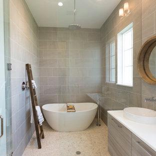 Ispirazione per una grande stanza da bagno padronale design con lavabo sottopiano, ante lisce, ante grigie, top in granito, vasca freestanding, piastrelle grigie, piastrelle in ceramica, pareti bianche, pavimento con piastrelle in ceramica e doccia a filo pavimento