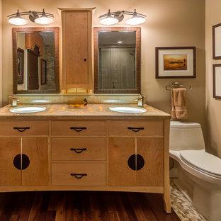 Ejemplo de cuarto de baño principal, de estilo zen, de tamaño medio, con armarios tipo mueble, puertas de armario de madera clara, baldosas y/o azulejos beige, suelo de baldosas tipo guijarro, suelo de madera oscura y encimera de ónix