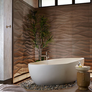 Large asian master brown tile and ceramic tile concrete floor and brown floor freestanding bathtub photo in Wichita with flat-panel cabinets, dark wood cabinets, beige walls, a vessel sink and glass countertops