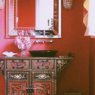 Foto di una stanza da bagno etnica di medie dimensioni con consolle stile comò, ante nere, pareti rosse, pavimento in travertino e lavabo a bacinella