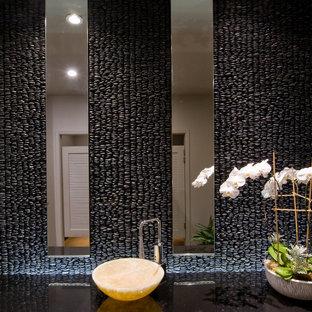Idee per una stanza da bagno minimal con lavabo a bacinella, top in marmo, piastrelle nere, piastrelle di ciottoli e pavimento in cemento