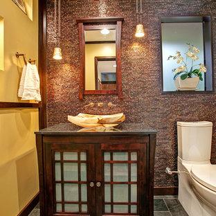 Immagine di una stanza da bagno con doccia etnica di medie dimensioni con lavabo a bacinella, ante di vetro, ante in legno bruno, top in granito, WC a due pezzi, pareti gialle, pavimento in ardesia, piastrelle marroni e piastrelle a mosaico