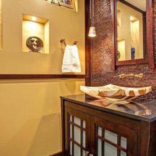 Imagen de cuarto de baño con ducha, asiático, de tamaño medio, con lavabo sobreencimera, armarios tipo vitrina, puertas de armario de madera en tonos medios, encimera de granito, sanitario de dos piezas, baldosas y/o azulejos marrones, baldosas y/o azulejos en mosaico y paredes amarillas
