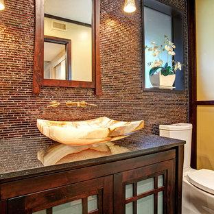 Esempio di una stanza da bagno con doccia etnica di medie dimensioni con lavabo a bacinella, ante di vetro, ante in legno bruno, top in granito, WC a due pezzi, piastrelle marroni, piastrelle a mosaico e pareti gialle