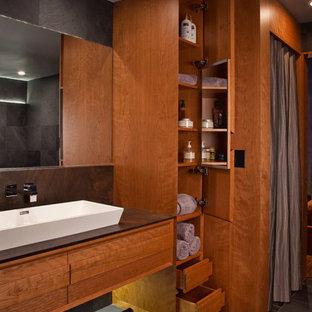 Foto di una grande stanza da bagno padronale design con lavabo rettangolare, consolle stile comò, ante in legno scuro, top in pietra calcarea e pavimento in ardesia