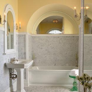 Imagen de cuarto de baño principal, clásico, con lavabo con pedestal, paredes amarillas, bañera empotrada, baldosas y/o azulejos grises, baldosas y/o azulejos de piedra, suelo de mármol y suelo multicolor