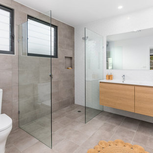 Photo of a 3/4 wet room bathroom in Other with flat-panel cabinets, medium wood cabinets, a two-piece toilet, beige tile, white tile, an integrated sink, beige floor, an open shower and white benchtops.