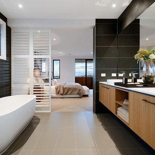Idee per una stanza da bagno padronale minimal con ante lisce, ante in legno chiaro, vasca freestanding, piastrelle nere, pareti nere e lavabo a bacinella