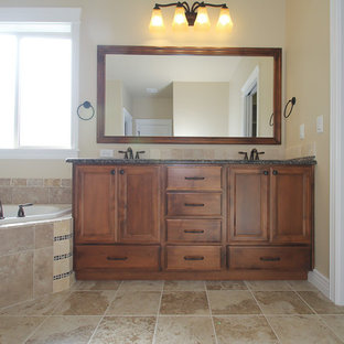 Example of a mid-sized arts and crafts master beige tile and ceramic tile ceramic floor bathroom design in Boise with a drop-in sink, flat-panel cabinets, medium tone wood cabinets, granite countertops, a one-piece toilet and beige walls