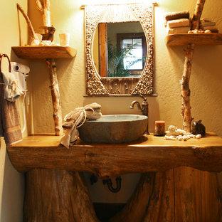 Ejemplo de cuarto de baño con ducha, rural, grande, con lavabo sobreencimera, armarios abiertos, puertas de armario con efecto envejecido, encimera de madera, ducha empotrada, sanitario de dos piezas, baldosas y/o azulejos beige, baldosas y/o azulejos de piedra, paredes amarillas y suelo de baldosas de cerámica