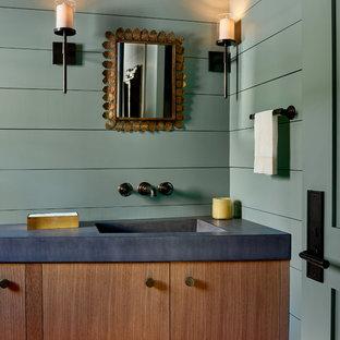 Diseño de cuarto de baño rural con armarios con paneles lisos, puertas de armario de madera oscura, paredes verdes, lavabo integrado y encimeras grises