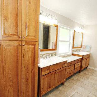 На фото: большая главная ванная комната в классическом стиле с фасадами с выступающей филенкой, светлыми деревянными фасадами, разноцветной плиткой, бежевыми стенами, полом из керамической плитки, монолитной раковиной и столешницей из искусственного кварца с