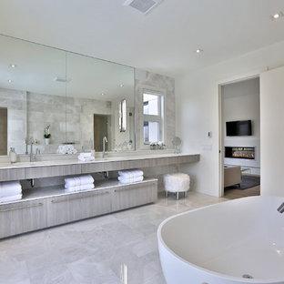 Idee per un'ampia stanza da bagno padronale contemporanea con ante lisce, ante in legno chiaro, vasca freestanding, pareti bianche, lavabo sottopiano, piastrelle grigie, piastrelle in pietra, pavimento in marmo e top in marmo