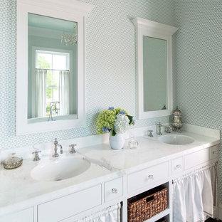 Cette image montre une salle de bain principale rustique avec des portes de placard blanches, un mur multicolore, un lavabo encastré, un sol marron et un plan de toilette blanc.