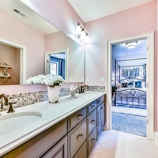 シャーロットの広いトランジショナルスタイルのおしゃれな子供用バスルーム (落し込みパネル扉のキャビネット、濃色木目調キャビネット、珪岩の洗面台、ベージュのタイル、ピンクの壁) の写真