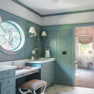 Inspiration pour une douche en alcôve traditionnelle de taille moyenne avec des portes de placard bleues, une baignoire indépendante, un carrelage gris, un mur bleu, un sol en carrelage de porcelaine, un lavabo encastré, un plan de toilette en surface solide, un sol multicolore, aucune cabine, un placard à porte shaker, meuble-lavabo encastré et du lambris.