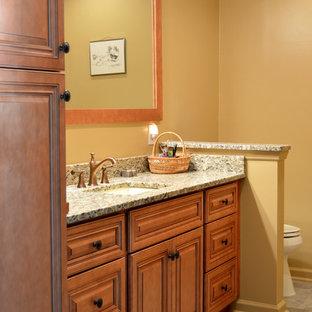 アトランタの小さいトランジショナルスタイルのおしゃれなマスターバスルーム (アンダーカウンター洗面器、レイズドパネル扉のキャビネット、中間色木目調キャビネット、御影石の洗面台、アルコーブ型シャワー、一体型トイレ、ベージュのタイル、磁器タイル、黄色い壁、磁器タイルの床) の写真