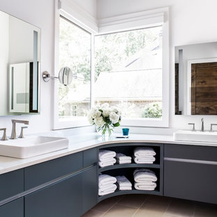 Photo of a rural bathroom in Atlanta with flat-panel cabinets, grey cabinets, white walls, a vessel sink, beige floors and white worktops.