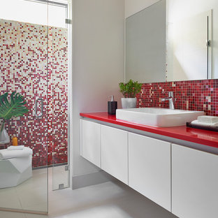 Example of a mid-sized trendy 3/4 multicolored tile and mosaic tile porcelain floor and gray floor walk-in shower design in Atlanta with flat-panel cabinets, white cabinets, white walls, a vessel sink, quartz countertops, a hinged shower door, a one-piece toilet and red countertops
