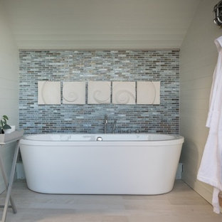 Photo of a small coastal bathroom in Cornwall with a freestanding bath, white walls and beige floors.