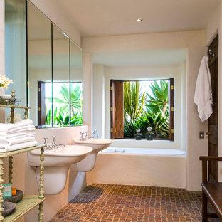 Ispirazione per una stanza da bagno eclettica con lavabo sospeso, vasca ad alcova, pareti bianche e pavimento in mattoni