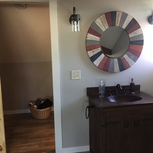 Example of a mid-sized mountain style 3/4 brown floor and medium tone wood floor bathroom design in Milwaukee with gray walls, furniture-like cabinets, dark wood cabinets, solid surface countertops, a two-piece toilet and an integrated sink