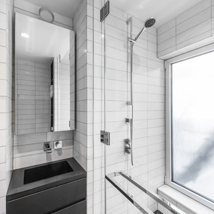 Example of a small minimalist master black and white tile and stone tile marble floor alcove shower design in New York with flat-panel cabinets, black cabinets, a one-piece toilet, white walls, an integrated sink and solid surface countertops