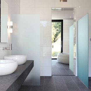 Bild på ett mycket stort funkis grå grått en-suite badrum, med ett fristående handfat, ett fristående badkar, en öppen dusch, grå kakel, vit kakel, porslinskakel, vita väggar, klinkergolv i porslin, bänkskiva i betong och med dusch som är öppen