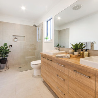 Contemporary master bathroom in Sunshine Coast with an open shower, a one-piece toilet, beige tile, cement tile, white walls, ceramic floors, beige floor and a vessel sink.