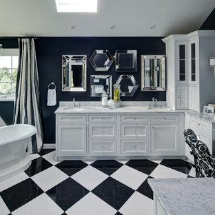 Modelo de cuarto de baño tradicional con lavabo bajoencimera, armarios estilo shaker, puertas de armario blancas, bañera exenta, paredes negras y suelo multicolor