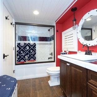 Idee per una stanza da bagno tradizionale di medie dimensioni con ante con bugna sagomata, ante in legno scuro, vasca ad alcova, vasca/doccia, WC a due pezzi, piastrelle blu, piastrelle diamantate, pareti rosse, pavimento con piastrelle in ceramica, lavabo da incasso e top piastrellato