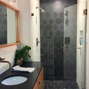 Idéer för ett litet modernt badrum med dusch, med släta luckor, skåp i mellenmörkt trä, en kantlös dusch, svart kakel, cementkakel, vita väggar, cementgolv, ett undermonterad handfat och granitbänkskiva