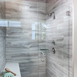 Mid-sized farmhouse master gray tile and porcelain tile plywood floor bathroom photo in Austin with recessed-panel cabinets, white cabinets, a one-piece toilet, gray walls, an undermount sink and solid surface countertops