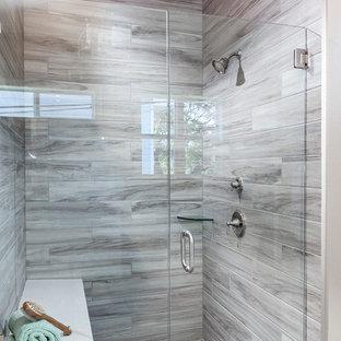 Réalisation d'une salle de bain principale champêtre de taille moyenne avec un placard avec porte à panneau encastré, des portes de placard blanches, une baignoire indépendante, une douche à l'italienne, un WC à poser, un carrelage gris, des carreaux de porcelaine, un mur gris, un sol en contreplaqué, un lavabo encastré et un plan de toilette en surface solide.