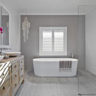 Ispirazione per una stanza da bagno padronale design di medie dimensioni con ante in legno chiaro, vasca freestanding, zona vasca/doccia separata, piastrelle grigie, piastrelle di vetro, pareti bianche, pavimento in gres porcellanato, lavabo a bacinella, pavimento grigio e doccia aperta