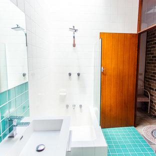 Idee per una stanza da bagno con doccia tropicale di medie dimensioni con lavabo integrato, ante a filo, ante bianche, top in superficie solida, vasca ad angolo, doccia ad angolo, WC sospeso, piastrelle blu, piastrelle di vetro, pareti bianche e pavimento con piastrelle in ceramica