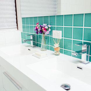 Mittelgroßes Tropisches Duschbad mit integriertem Waschbecken, Kassettenfronten, weißen Schränken, Mineralwerkstoff-Waschtisch, Eckbadewanne, Eckdusche, Wandtoilette, blauen Fliesen, Glasfliesen, weißer Wandfarbe und Keramikboden in Sydney