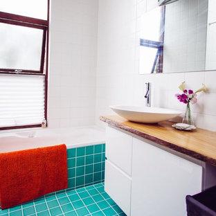 Esempio di una stanza da bagno con doccia tropicale di medie dimensioni con lavabo integrato, ante a filo, ante bianche, top in superficie solida, vasca ad angolo, doccia ad angolo, WC sospeso, piastrelle blu, piastrelle di vetro, pareti bianche e pavimento con piastrelle in ceramica