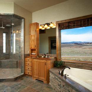 На фото: большие главные ванные комнаты в стиле кантри с фасадами с декоративным кантом, коричневыми фасадами, угловой ванной, угловым душем, разноцветной плиткой, каменной плиткой, бежевыми стенами, полом из керамогранита, накладной раковиной, столешницей из меди, разноцветным полом и душем с распашными дверями
