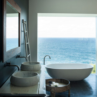 Photo of a beach style master bathroom in Sydney with furniture-like cabinets, beige cabinets, a freestanding tub, black walls, a vessel sink, wood benchtops, black floor and white benchtops.