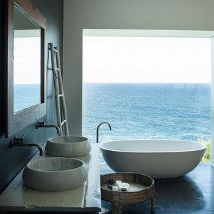 Imagen de cuarto de baño principal, marinero, con armarios tipo mueble, puertas de armario beige, bañera exenta, paredes negras, lavabo sobreencimera, encimera de madera, suelo negro y encimeras blancas