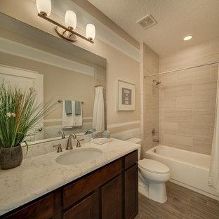 Esempio di una stanza da bagno con doccia classica di medie dimensioni con ante in stile shaker, ante in legno bruno, vasca ad alcova, vasca/doccia, WC a due pezzi, pareti beige, pavimento in laminato, lavabo sottopiano, top in marmo e doccia con tenda
