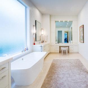 Idéer för att renovera ett mycket stort funkis en-suite badrum, med ett undermonterad handfat, släta luckor, vita skåp, bänkskiva i onyx, ett fristående badkar, en kantlös dusch, en toalettstol med hel cisternkåpa, vit kakel, stenkakel, beige väggar och kalkstensgolv
