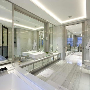 This is an example of an expansive traditional ensuite bathroom in London with a vessel sink, flat-panel cabinets, marble worktops, a bidet, grey tiles, grey walls, marble flooring and marble tiles.