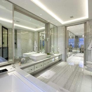 Foto de cuarto de baño principal, clásico renovado, extra grande, con lavabo sobreencimera, armarios con paneles lisos, encimera de mármol, bidé, baldosas y/o azulejos grises, paredes grises, suelo de mármol y baldosas y/o azulejos de mármol