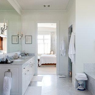 Klassisk inredning av ett stort grå grått en-suite badrum, med luckor med upphöjd panel, vita skåp, ett platsbyggt badkar, en toalettstol med hel cisternkåpa, grå kakel, vit kakel, vita väggar, marmorgolv, ett undermonterad handfat, marmorbänkskiva och marmorkakel