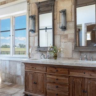 Landhaus Badezimmer mit Schrankfronten mit vertiefter Füllung, hellbraunen Holzschränken, Löwenfuß-Badewanne, beigefarbenen Fliesen, Unterbauwaschbecken, beigem Boden und beiger Waschtischplatte in Denver